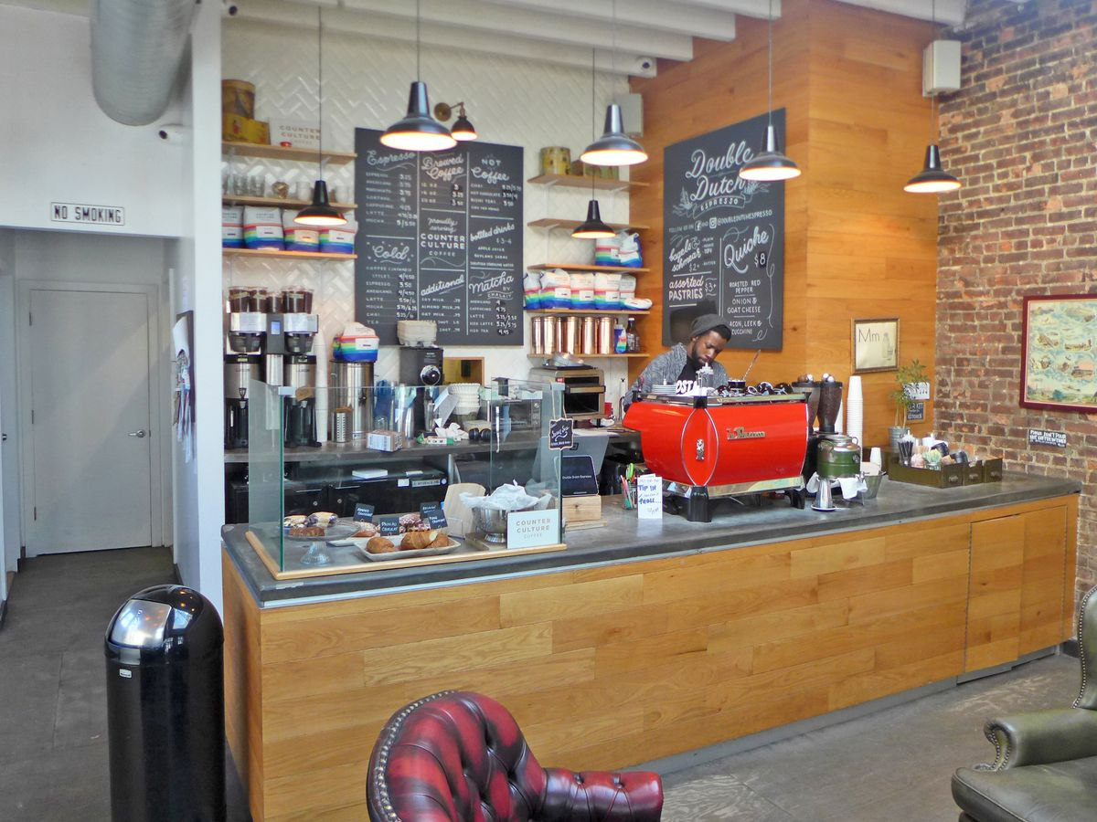 A counter, an espresso machine, and a barista.
