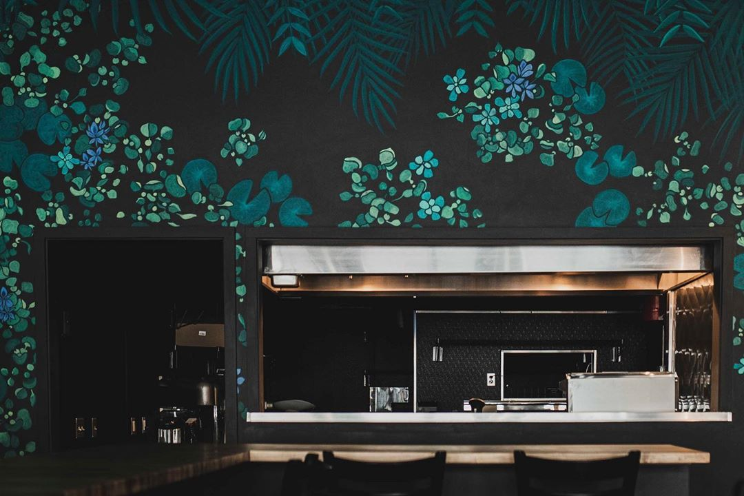 a restaurant interior featuring dark walls covered with painted leafy green plants