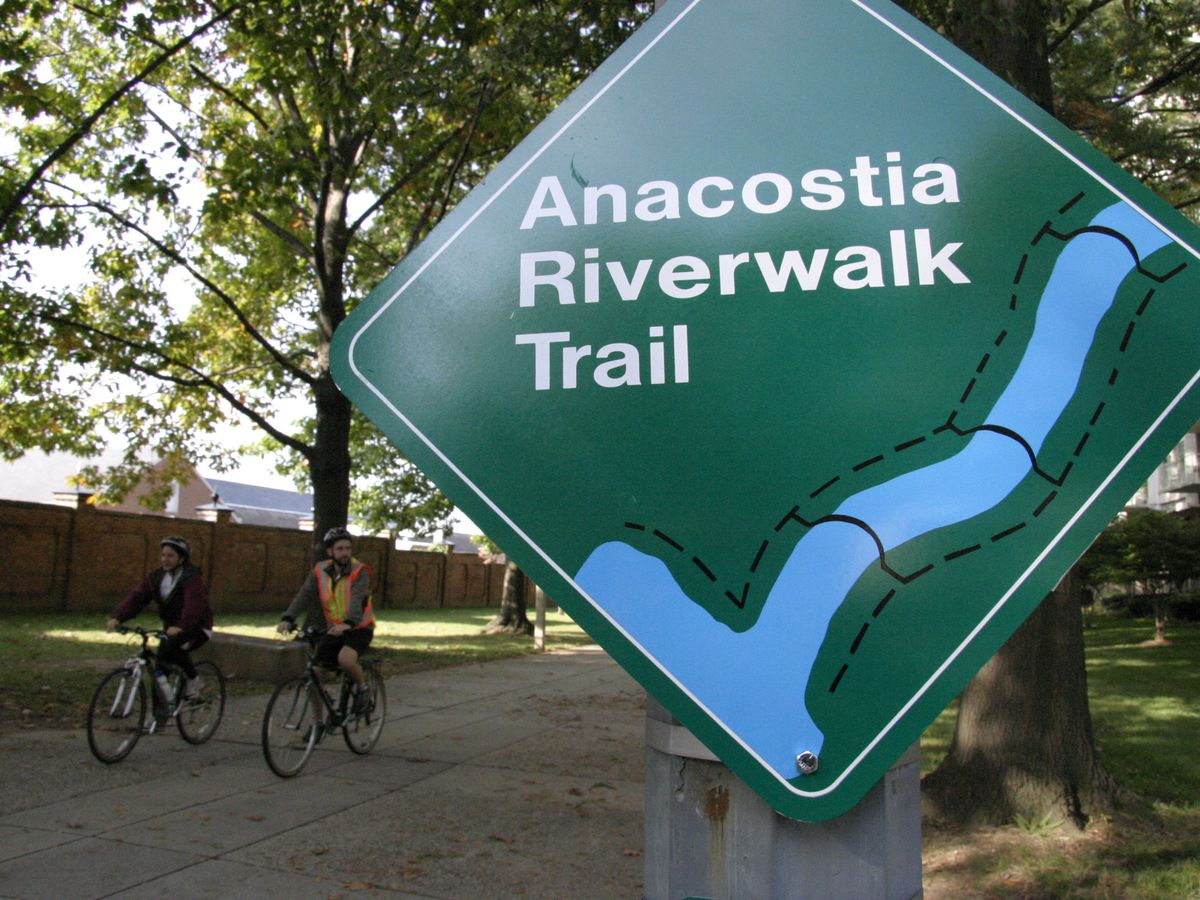 People ride bicycles down a bike path. In the foreground is a green sign with the words: Anacostia Riverwalk Trail.