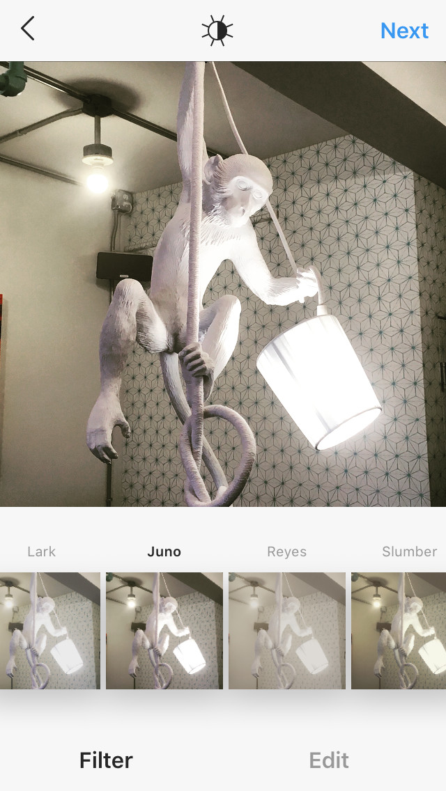 a hanging monkey sculpture holding a working lamp