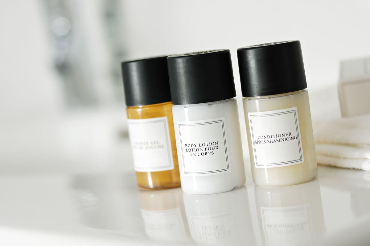 Tiny hotel shampoo bottles on a countertop.