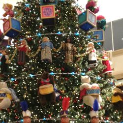 Toys featured on the tree include teddy bears, rocking horses, toy soldiers, dolls, and toy tops.