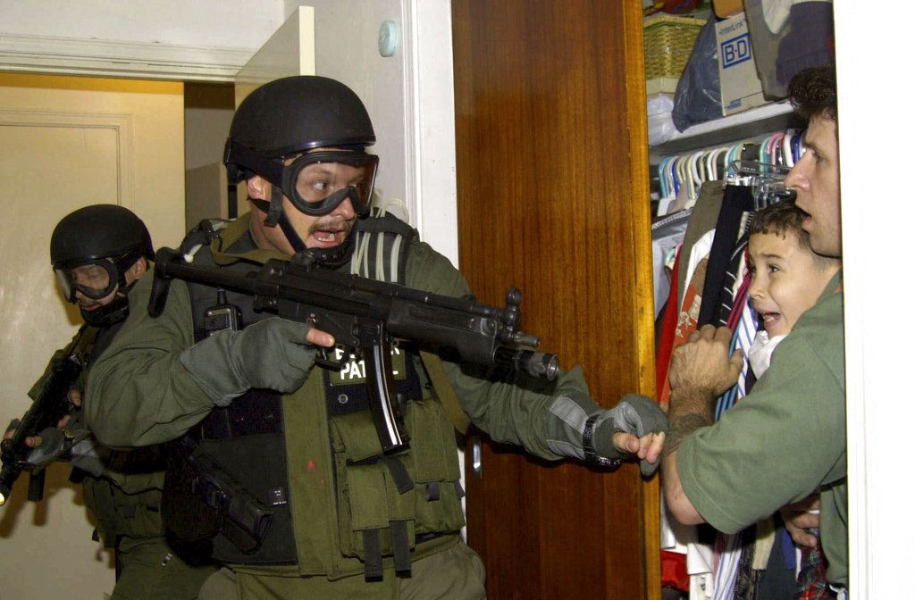 In this April 22, 2000 photo, by Associated Press photojournalist Alan Diaz, Elian Gonzalez is held in a closet by Donato Dalrymple, one of the two men who rescued the boy from the ocean, right, as government officials search the home of Lazaro Gonzalez f