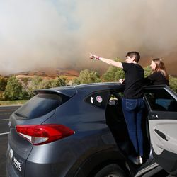 Spectators looks at the fire along East Provo Canyon Road in Orem on Saturday, Oct. 17, 2020.