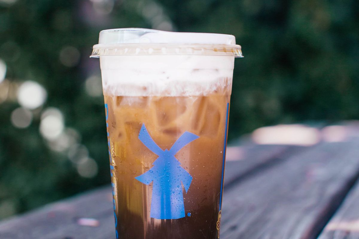 A plastic cup filled with iced coffee. A sprig of lavender sits in the foreground.