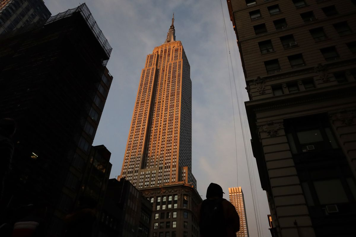 The empire state building can be seen in the center in golden light whereas the buildings around it are in shadow.