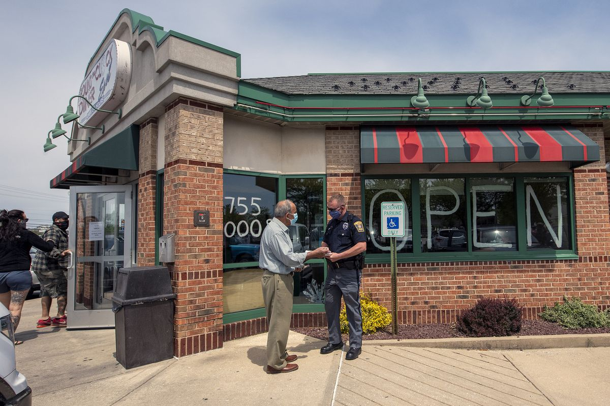 Around the Clock Diner owner Demos Sacarellos, left, talks with a Springettsbury Township Police officer after 911 received complaints about the diner opening Sunday, May 10, 2020, for sit-down service. The diner opened despite a Pennsylvania stay-at-home lockdown.