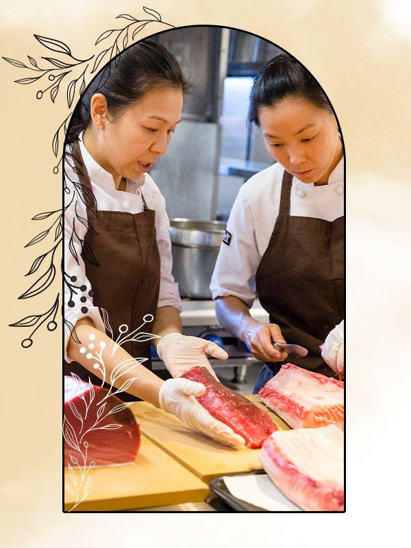N/Naka photo illustration of chefs Niki and Carole Nakayama processing raw fish.