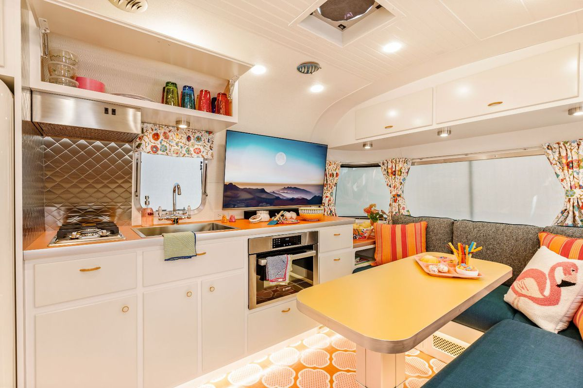 A view of the dinette area with a white kitchen cabinets and orange countertops.