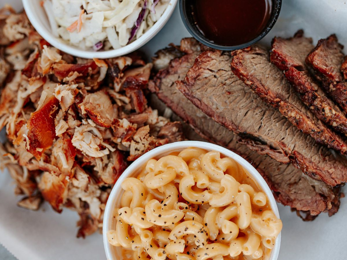 A plate of pulled pork and brisket with coleslaw and macaroni and cheese.