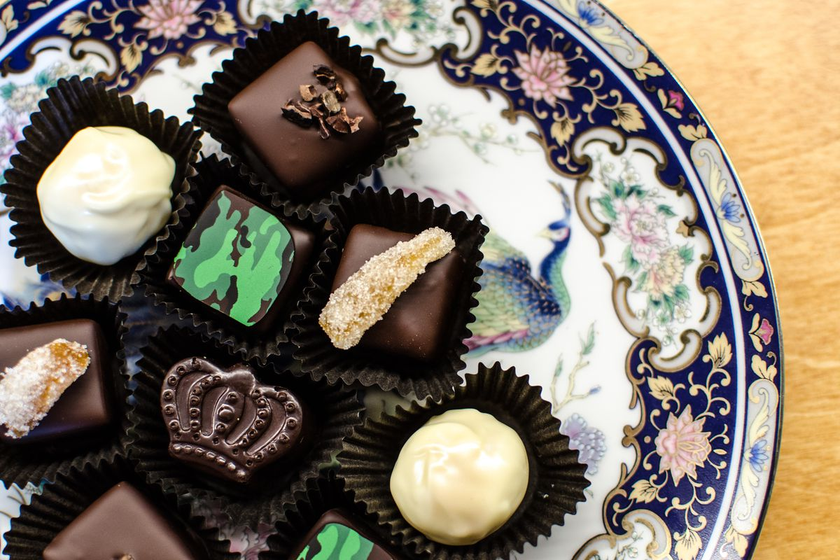 Several fancy chocolates sit on an elaborate peacock plate. One chocolate is crown-shaped, several are garnished with candied ginger, and several are garnished with a camo-patterned sliver of chocolate.