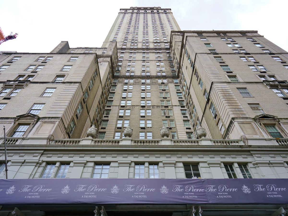 """A view of a grand hotel in New York City. The exterior is beige, and there is purple scaffolding at the bottom of the photo that reads """"The Pierre."""""""