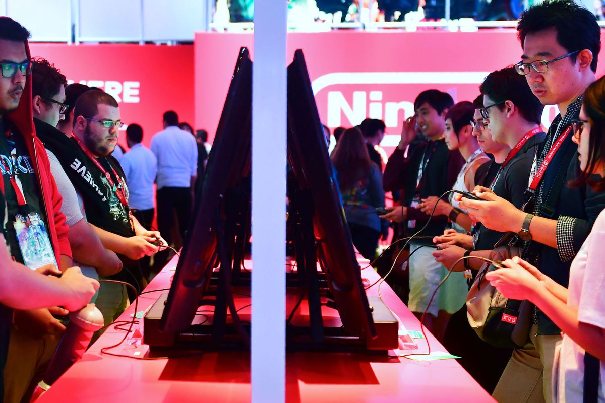 Gaming fans play Super Smash Bros on Nintendo Switch at the 24th Electronic Expo, or E3 2018, in Los Angeles, California on June 13, 2018 where hardware manufacturers, software developers and the video game industry present their new games at the 3-day ev