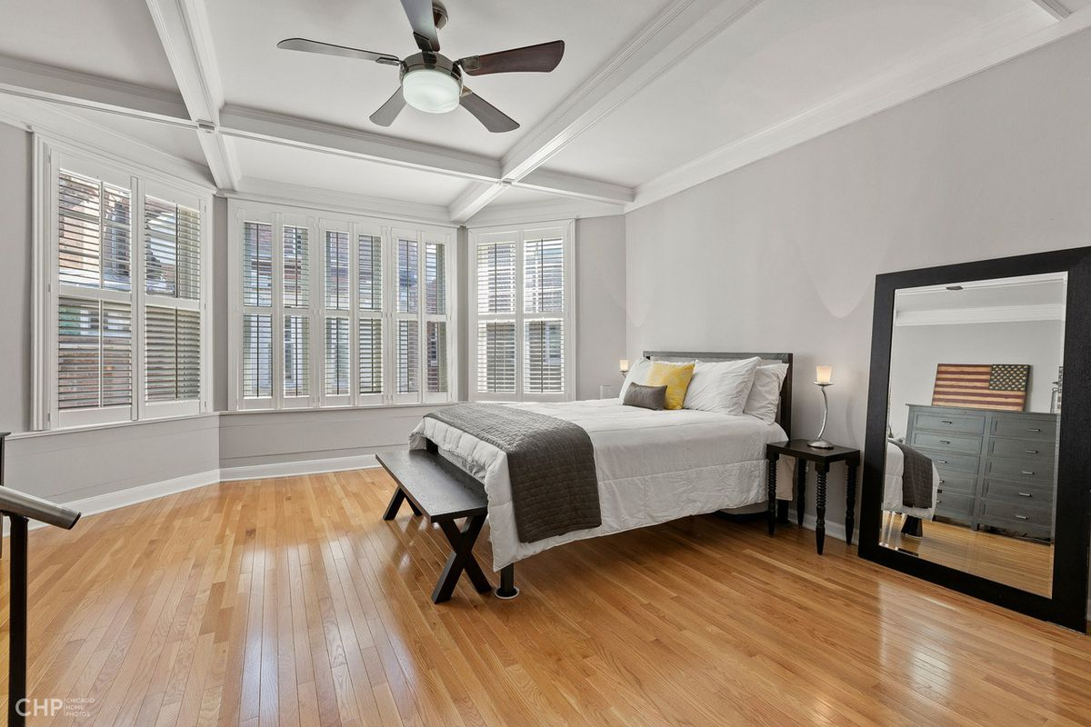 The bedroom has a large bay window, a floor mirror, and a bench in front of the bed.
