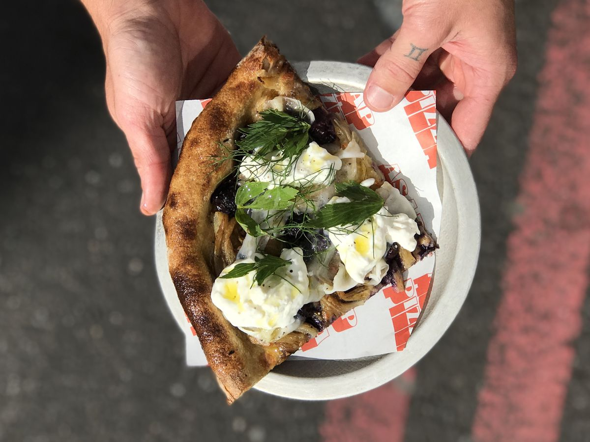 ASAP Pizza Borough Market shows off a slice of pizza with fragola grape, stracciatella, and fennel fronds held from a birdseye view over a road