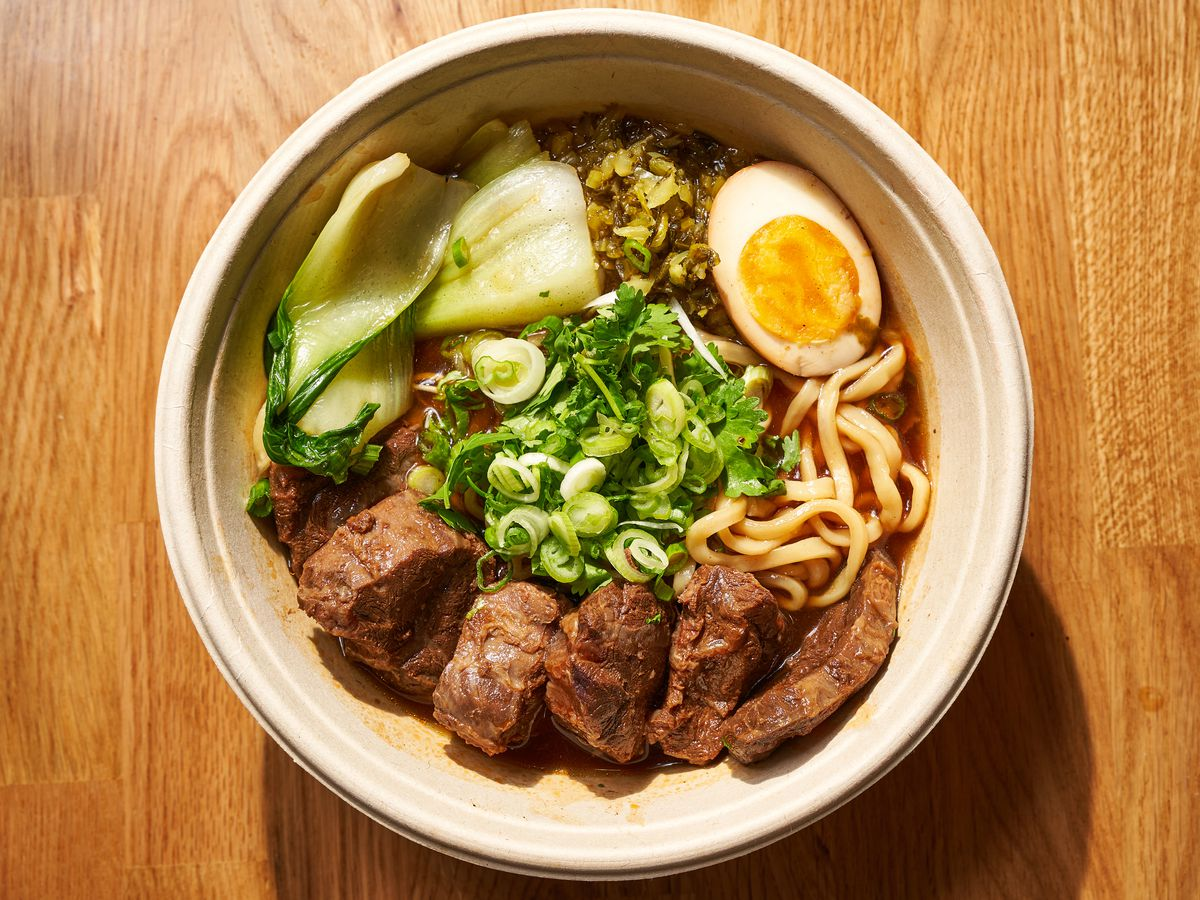 An overhead photograph of a bowl of soup with chunks of brown beef, noodles bok choy, a halved egg and mixed herbs