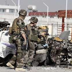 French soldiers arrive at the scene of a suicide bombing, Tuesday, Sept. 18, 2012 in Kabul, Afghanistan. A suicide bomber rammed a car packed with explosives into a mini-bus carrying foreign aviation workers to the airport in the Afghan capital early Tuesday, killing at least 12 people in an attack a militant group said was revenge for an anti-Islam film that ridicules the Prophet Muhammad.