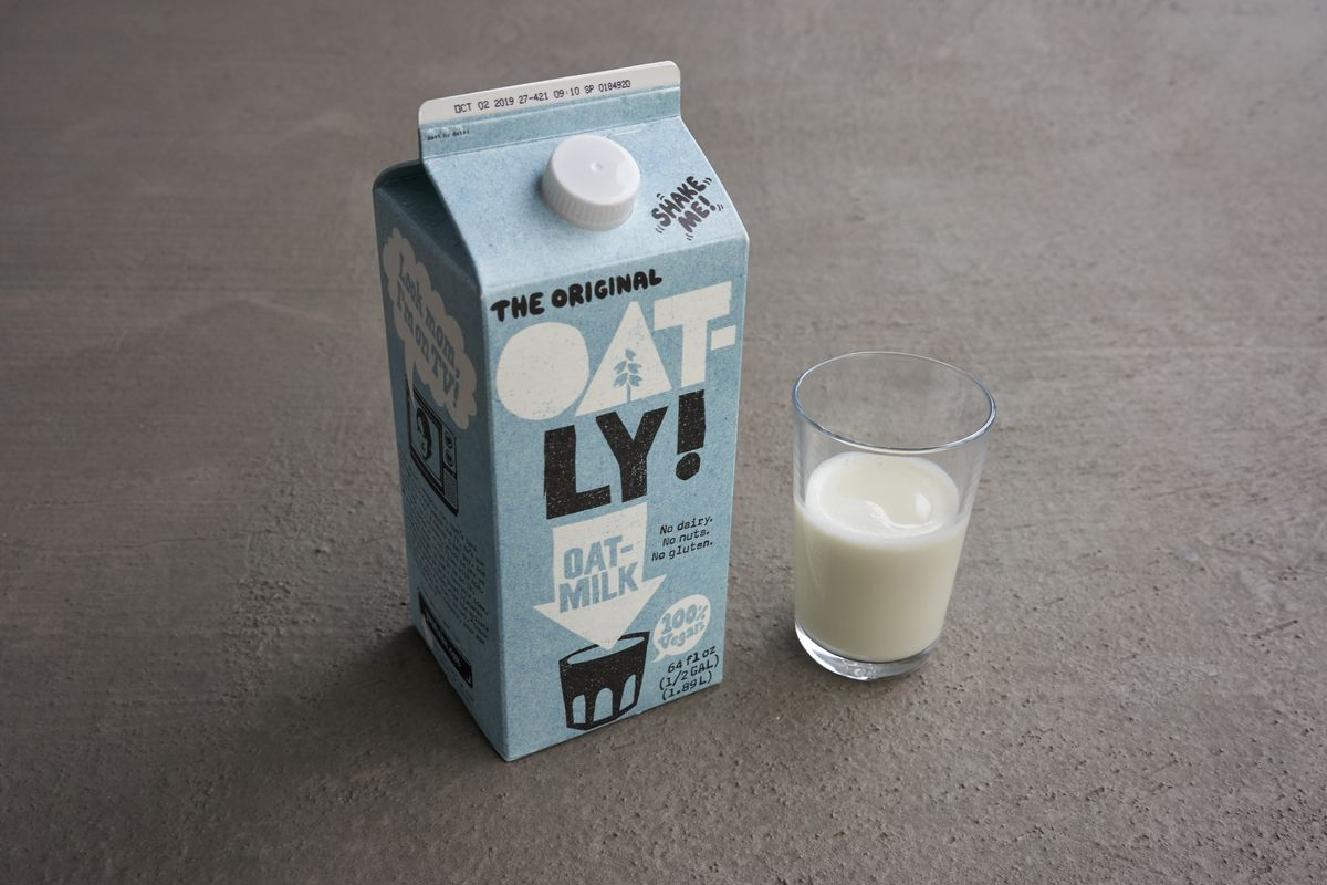 A carton and a glass of Oatly milk.
