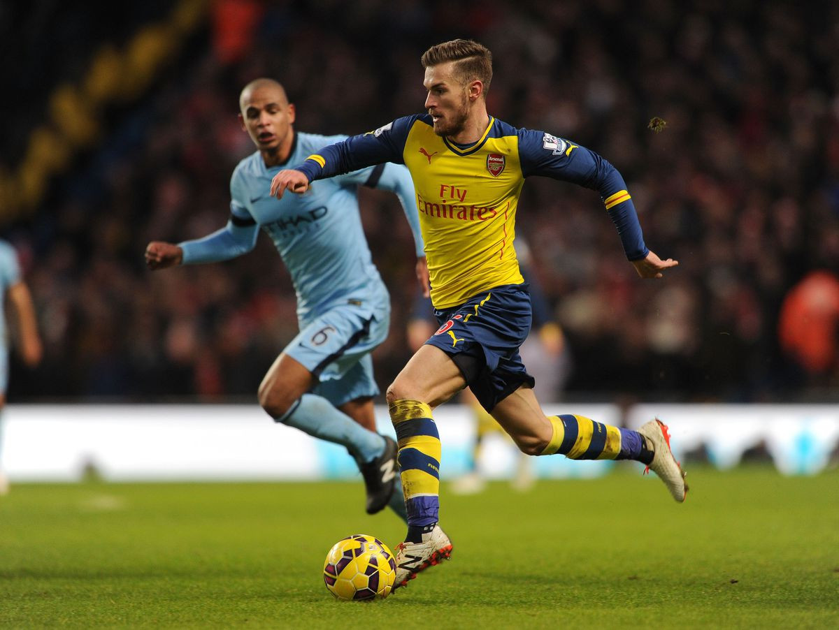 MANCHESTER, ENGLAND - JANUARY 18: Aaron Ramsey of Arsenal races away from Fernando of Man City during the match between Manchester City and Arsenal in the Barclays Premier League at Etihad Stadium on January 18, 2015 in Manchester, England. (Photo by Davi