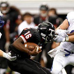 Bingham's Brandon Lambert, left, and teammate Braden Anderson work to bring down Euless (Texas) Trinity quarterback Willie Hubbard as the Miners play Trinity in the Kirk Herbstreit Varsity Football Series Monday at Dallas Cowboys Stadium in Arlington, Texas. Trinity won 42-21.