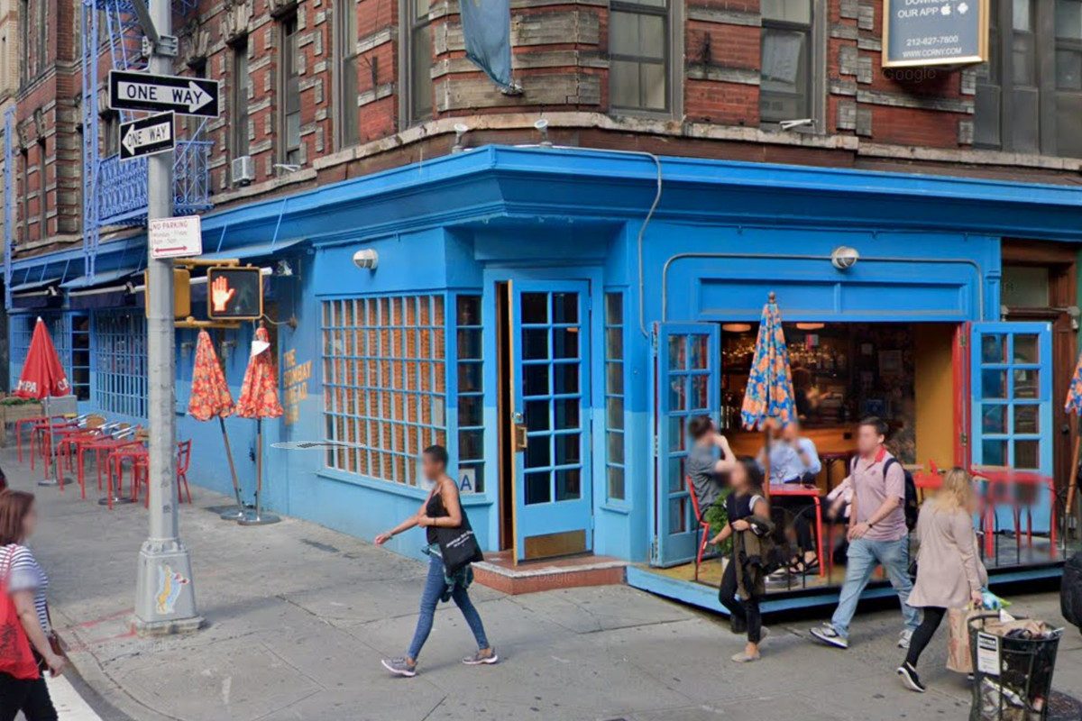 The exterior of a corner restaurant with blue paint outside and people walking on the sidewalk in front of it.