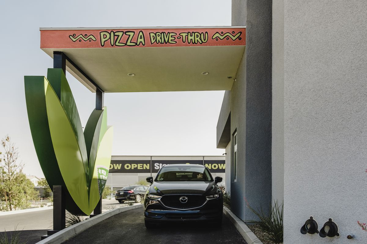 A drive-through next to a white building with a green wing sculpture.