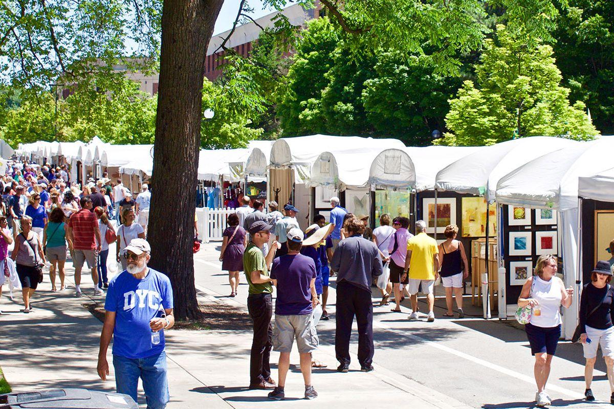 dozens of people walk around the ann arbor art fair's white tented booths
