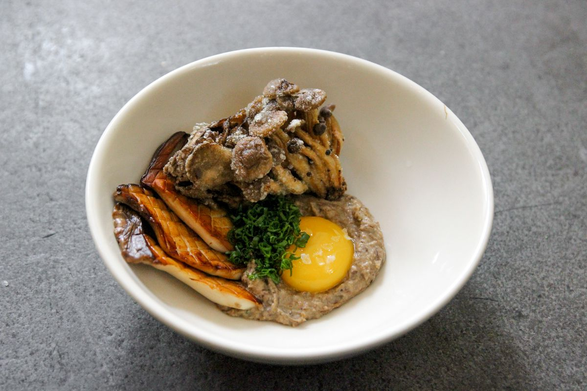 A white bowl with a mushroom dish in it with an egg yolk