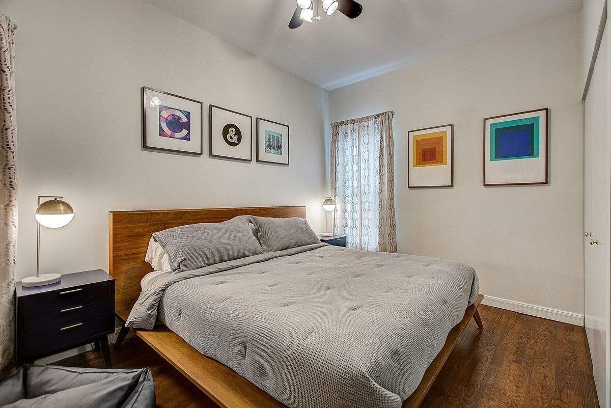 A bedroom with geometric, colorful art on the walls. There is a wood platform bed and two nightstands with table lamps.