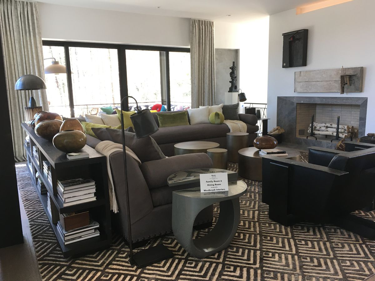 A huge family room wit black and grey furniture.