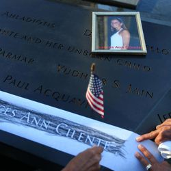 Judy Parisio, right, and Linda Malbrba, left, make a copy of the engraved name of their niece, Frances Ann Cilente, who worked and died at the World Trade Center as the giant flag came down at 1 World Trade Center during the commemoration ceremony of the 11th anniversary of the Sept. 11, 2001 terrorist attacks by the North Pool at World Trade Center in New York on Tuesday, Sept. 11, 2012.