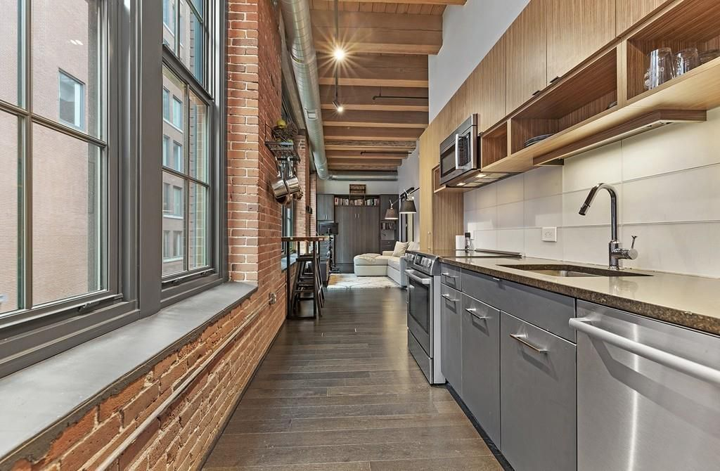 A longer view of the same studio with the narrow kitchen and its counter visible.