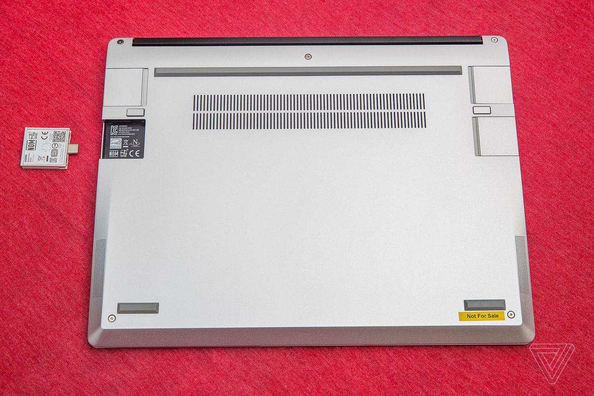 Karkasinis nešiojamas kompiuteris uždarytas, apverstas ant raudonos staltiesės.  Vienas iš keturių uosto lizdų yra tuščias.  Šalia tuščio prievado yra išplėtimo kortelė, apversta aukštyn kojom su QR kodu į viršų.