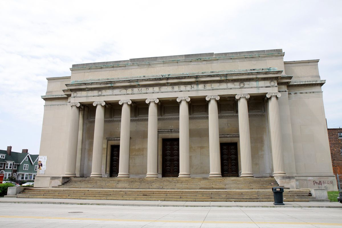 """A classical stone building with eight large columns in front of the portico. """"Temple Beth El"""" is written in the frieze."""