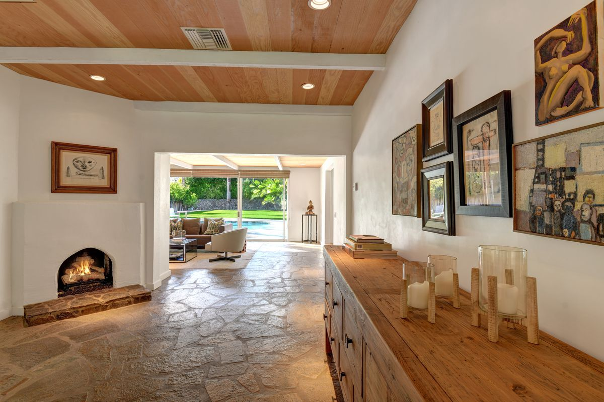 An entryway has a long wooden credenza, a fireplace, stone floors, and a hallway to the living room.
