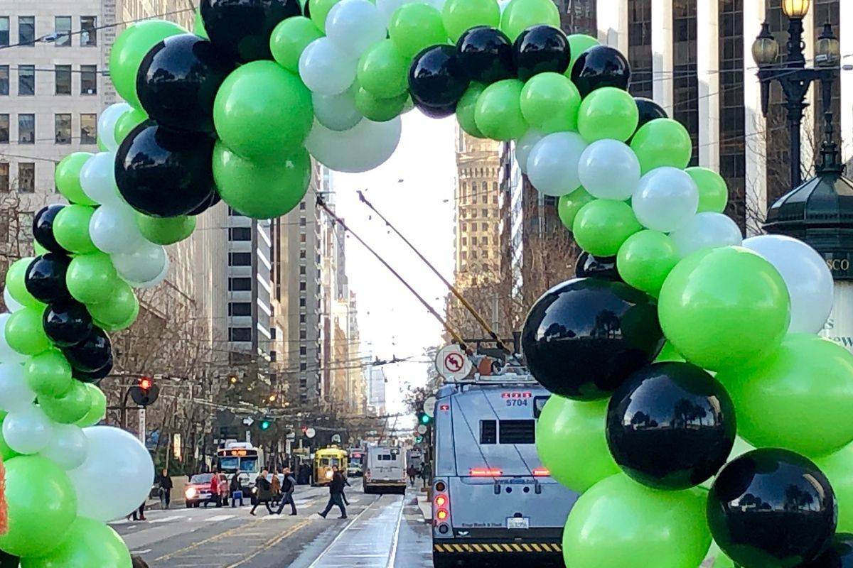 Black, white, and green balloons in an arch.