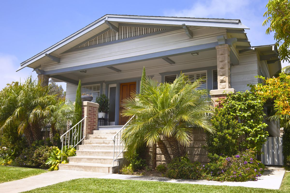 A home in California with concrete stairs leading up to front porch with large shrubs and blue trim.