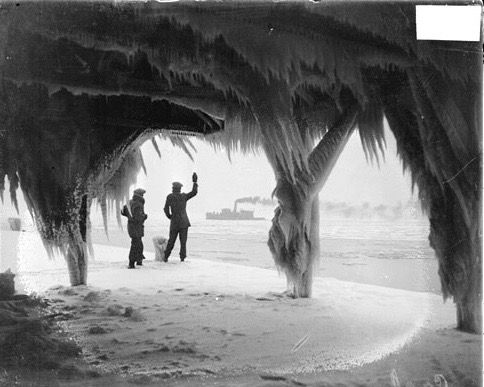 Image of water intake cribs by the lakeshore covered with ice from a storm inChicago,Illinois. Two figures are standing just beyond the cribs near the water. One has an arm raised. A steamer is visible on the water in the distance.
