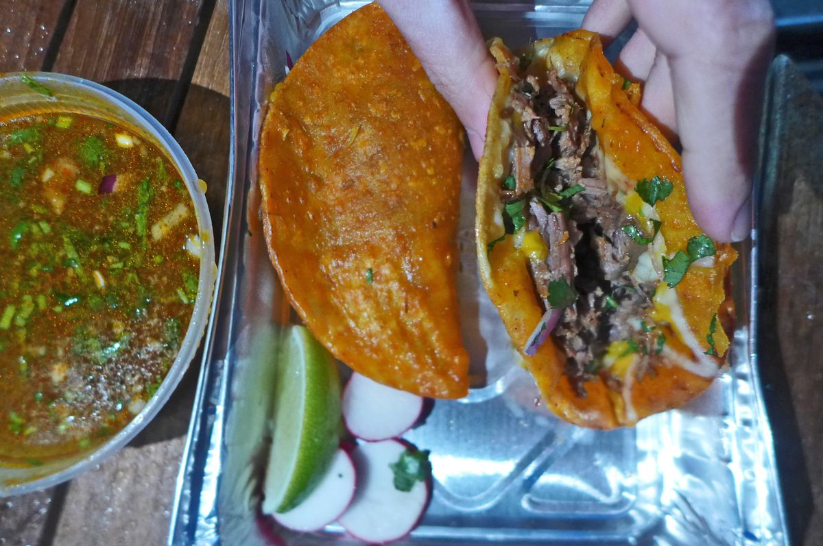 A hand holds a u-shaped taco with meat and cheese visible inside.