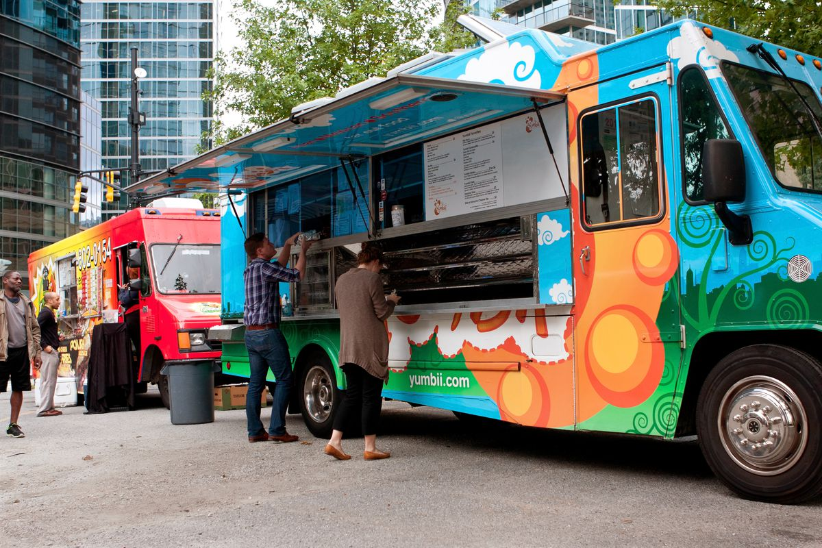 Two food trucks with people lined up at the windows