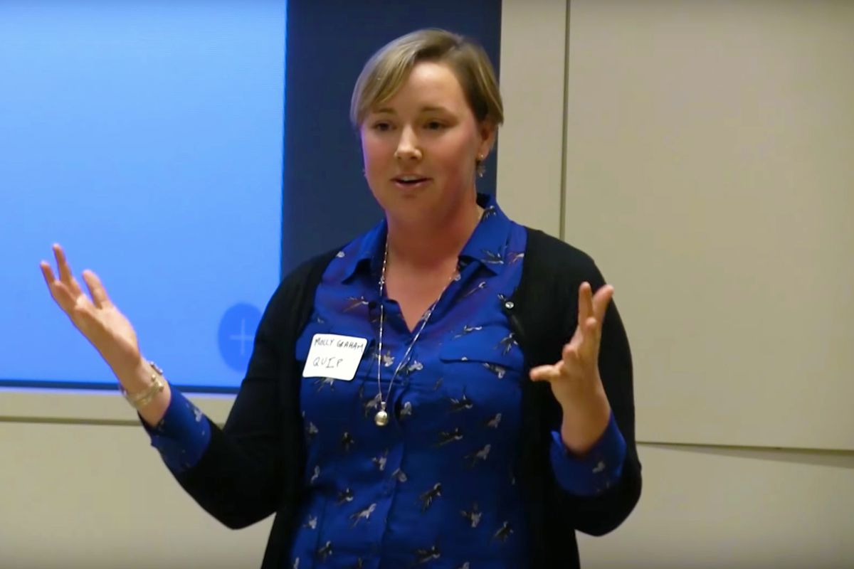 A caucasian woman in a blue shirt with short blonde hair gives a presentation at the front of a conference room.