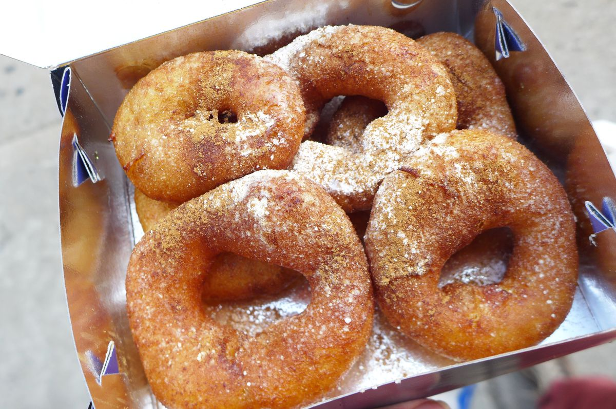 Four sugar-dusted loukoumades sit in a to-go box