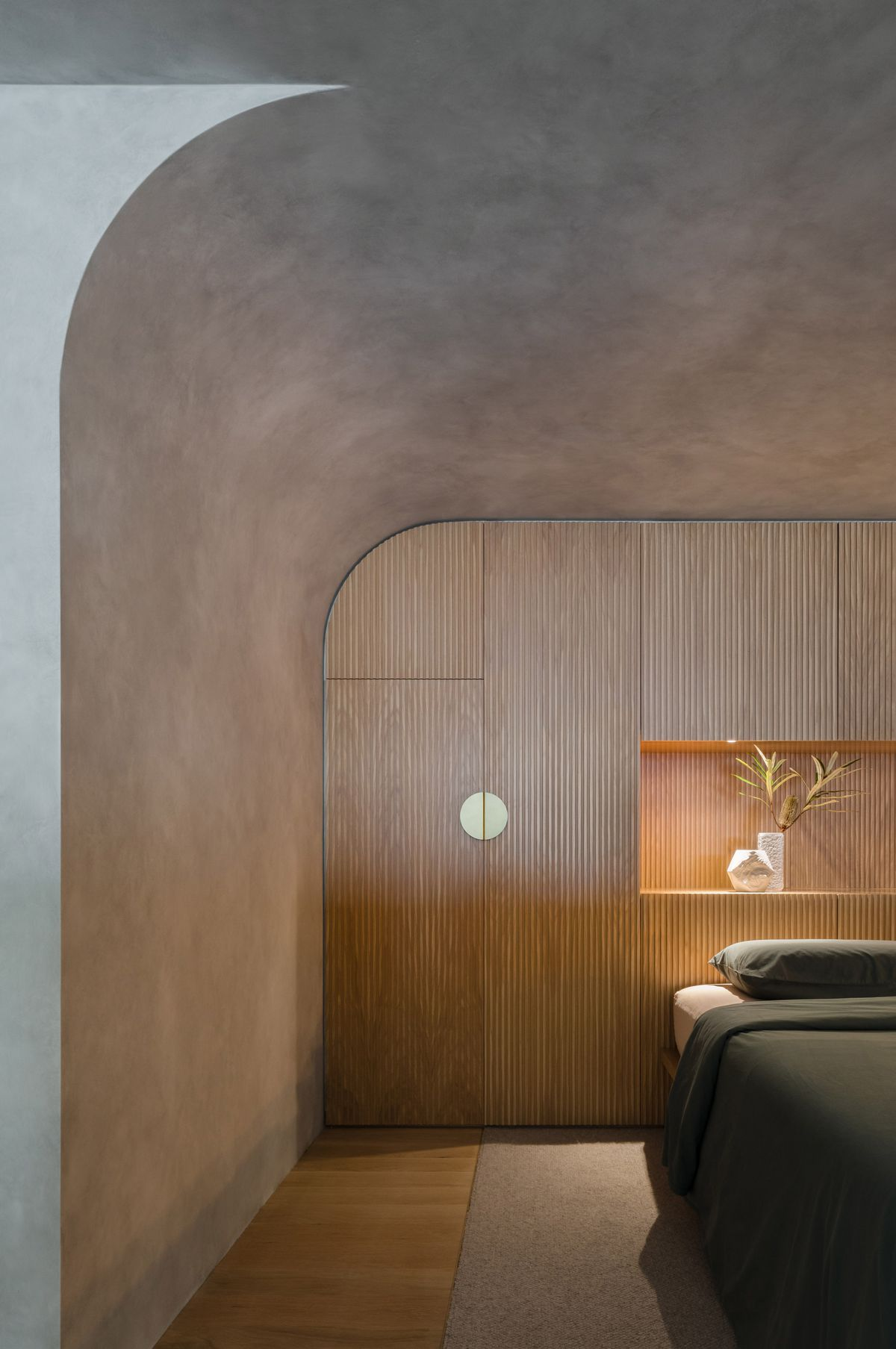 A bedroom area with concrete walls. There is a wooden headboard on one of the walls surrounding the bed.