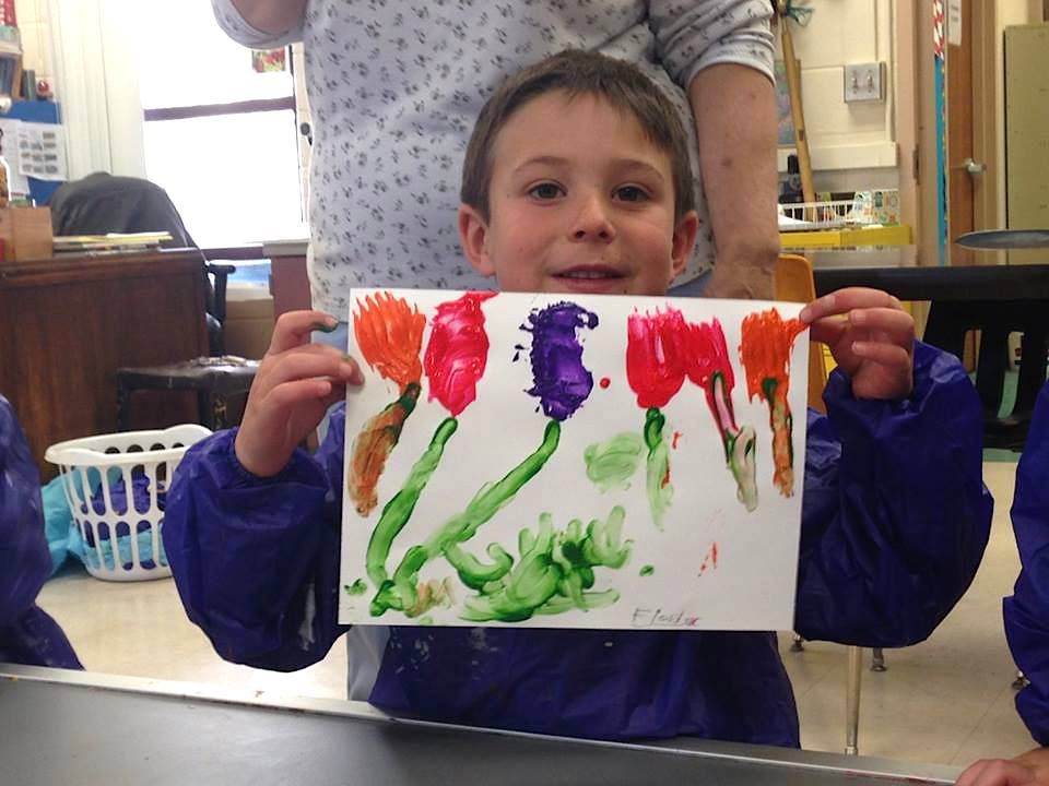 """A student in the """"Little Cubbies"""" program shows off his artwork during a session at Dolores Elementary School last February."""