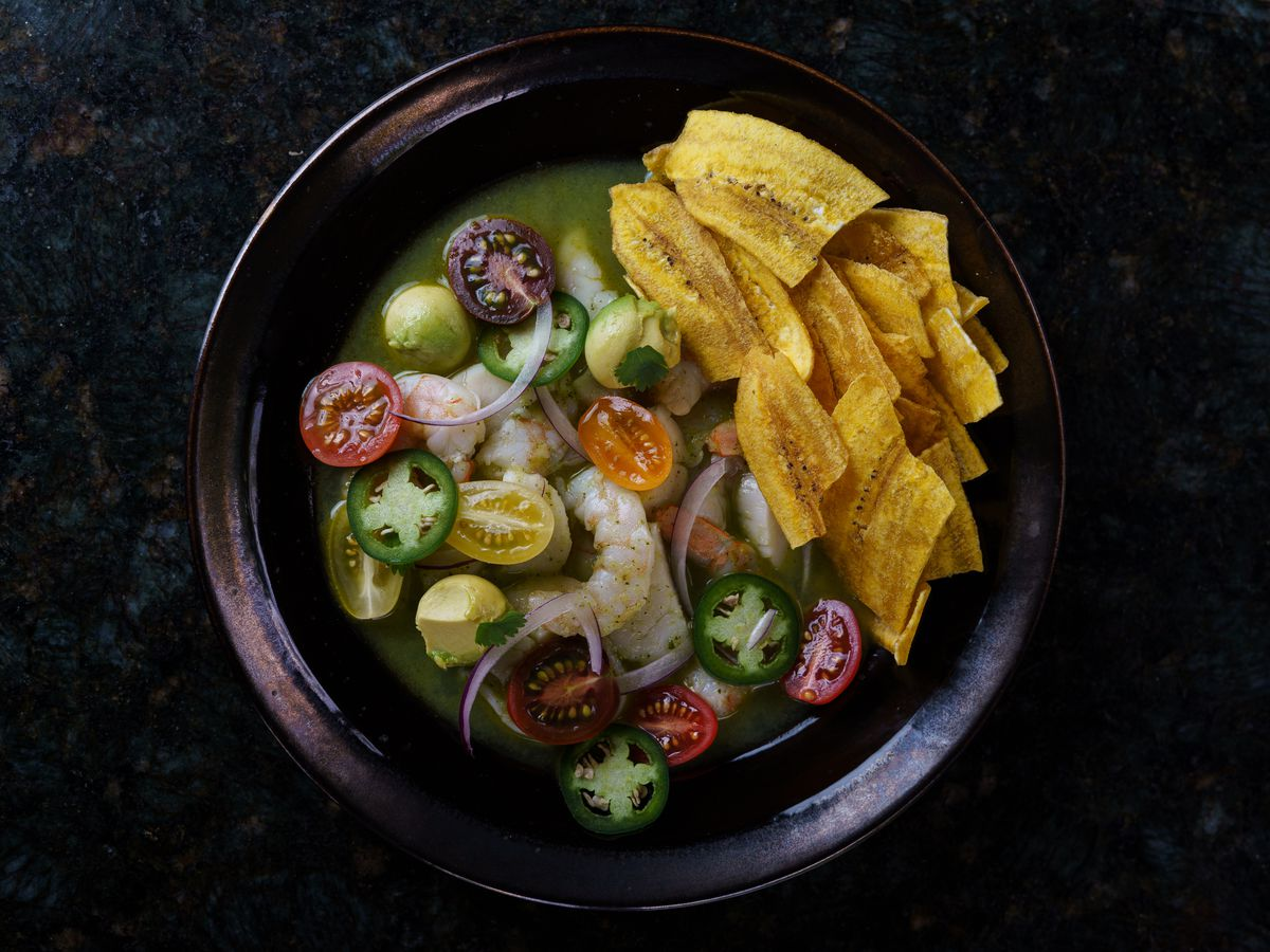 A bowl of fish, tomatoes, and plantain chips in broth on a dark background