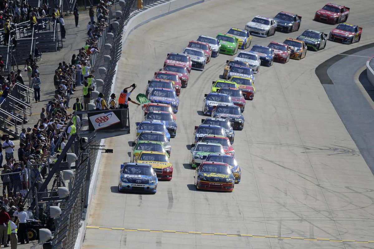 Racers take the green flag for the start of a NASCAR Sprint Cup Series auto race, Sunday, Sept. 30, 2012, at Dover International Speedway in Dover, Del.