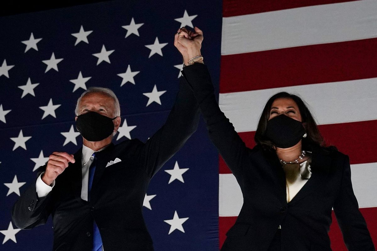 Joe Biden and Kamala Harris raise their held hands in front of a wall-sized American flag backdrop.