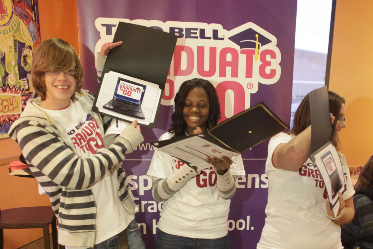 Three scholarship winners are given laptop computers.