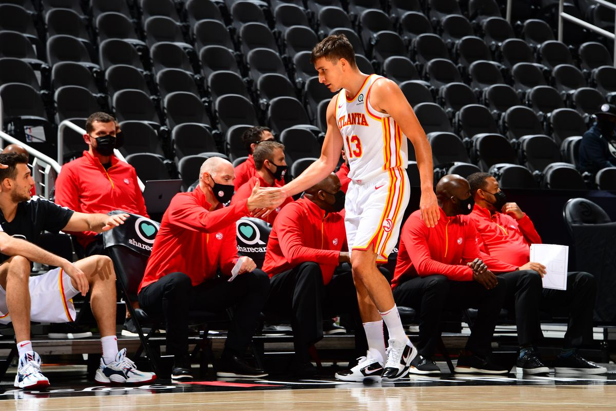 Bogdan Bogdanovic of the Atlanta Hawks high fives an assistant coach during the game against the Orlando Magic during a preseason game on December 11, 2020 at State Farm Arena in Atlanta, Georgia.