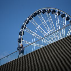 A person stands near the Ferris wheel at Navy Pier on its reopening day, Friday morning, April 30, 2021. Navy Pier was closed in 2020 due to the COVID-19 pandemic.